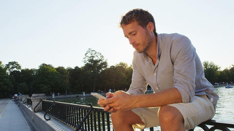 Man sms texting using app on smart phone at sunset in city park Live Action