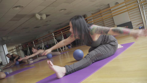 Live camera follows movement of confident brunette woman training people in yoga Live Action
