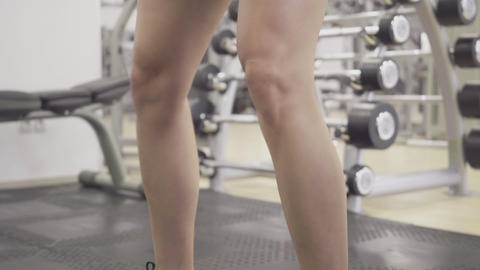 Close-up of slim female legs in shorts squatting. Unrecognizable young Caucasian Live Action