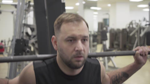 Close-up of concentrated Caucasian sportsman training in gym. Front view Live Action