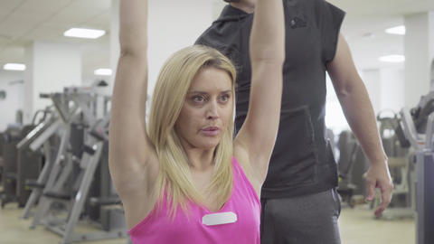 Unrecognizable trainer controls workout of slim blond Caucasian sportswoman with Live Action