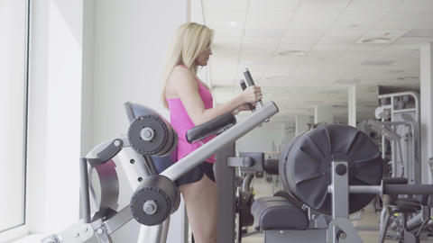 Wide shot of charming blond sportswoman exercising in sports club on equipment Live Action
