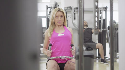 Portrait of blond young sportswoman pulling sport equipment in gym. Front view Live Action