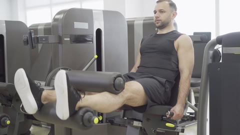 Confident young sportsman using sport equipment for leg training in gym Live Action