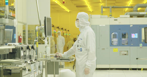 Workers in clean suits in a semiconductor manufacturing facility Footage