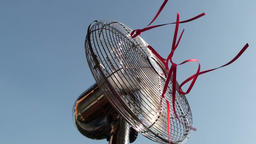 Metal fan with red strings attached swinging Footage