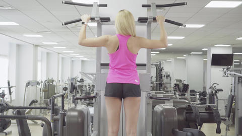 Back view of slim blond woman pulling up in gym. Camera follows movement of Live Action