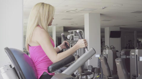 Side view of confident blond woman raising legs in gym. Young beautiful Live Action