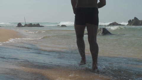 man does jogging along ocean shallow splashing water Live Action