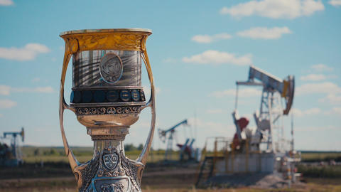 golden and yellow cup against large pump jacks in oil field ライブ動画
