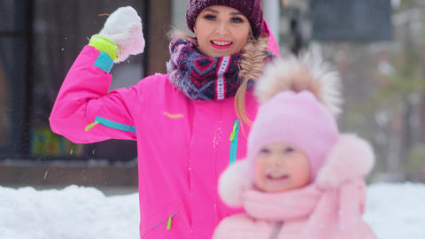 woman throws snowball and little girl kid smiles Live Action