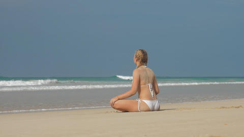 woman sits in lotus asana holds knees and looks at ocean Live Action