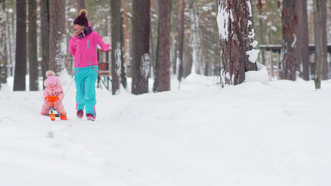 woman runs along snowy park path and carries sled with kid Live Action