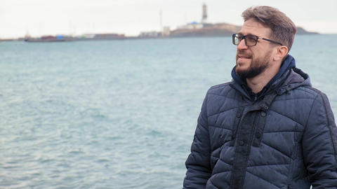 bearded man in glasses standing against the blue cold sea Live Action