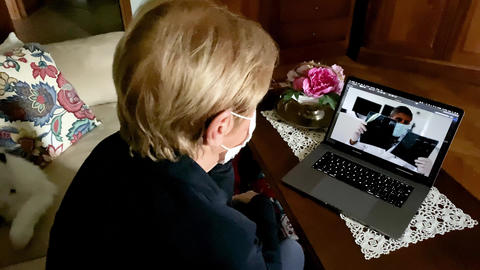 Elderly woman at home weaing mask in coronavirus times on a videocall with her Acción en vivo