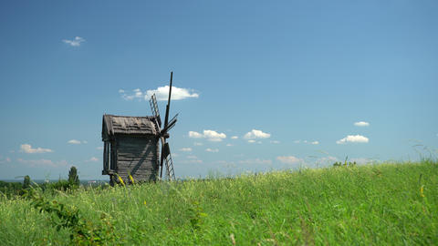 Old windmill on a green meadow, field. Blue sky with fast flowing clouds. Timelapse Live Action
