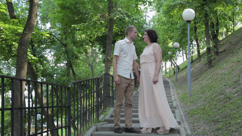 Young lovers on the stairs in the park GIF