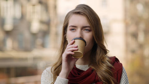 Smiling girl face drinking coffee outdoors. Pretty woman sipping hot drink Live Action