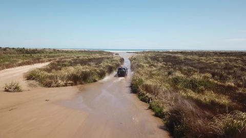 A 4WD runs on wet dirt road Te Paki Stream in New Zealand 2 Live Action