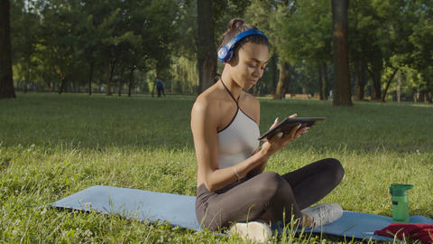 Female in headphones with tablet pc relaxing outdoor Live Action