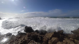 Waves rolling over breaker to rocky shore Live Action