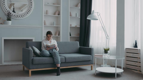 In stylish, modern, bright living room, young european mother is reading book on Live Action