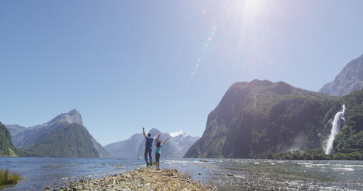 Couple celebrating jumping having fun outdoors in Milford Sound New Zealand Live Action