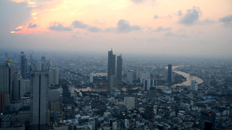 Panning high view of the city in sunset time / High view of Bangkok city in sunset Live Action