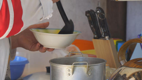 Woman pouring soup into a plate Live Action