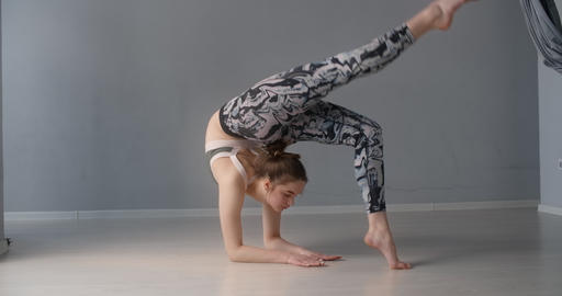Attractive young woman bends over forward and performs various yoga and Live Action
