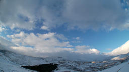 Clouds time lapse over snowy mountains Footage