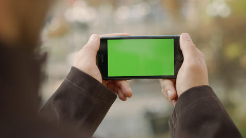 Man hands touching cellphone with greenscreen. Unknown guy holding mock up phone Live Action