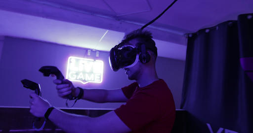 The guy is playing virtual reality games. Neon room for cyber sports Live Action