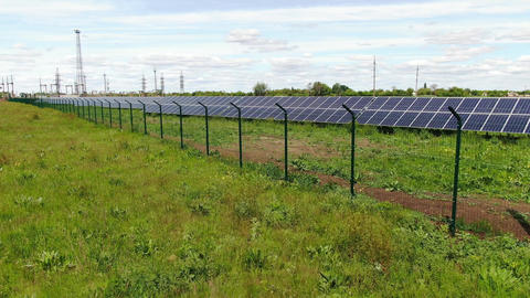Aerial view over the fence of the solar power station in the field, 4k Live Action