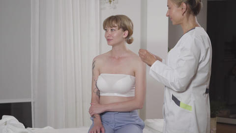 Adult concentrated doctor inserting acupuncture seeds into ear of smiling female Live Action