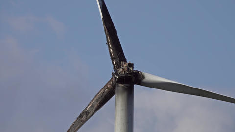 Burned damaged wind turbine against blue sky Live Action