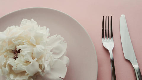 Beige table setting with peony flowers on plate and silverware for luxury dinner Live Action