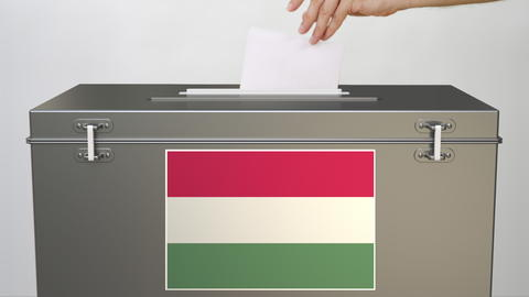 Putting paper ballot into ballot box with flag of Hungary. Voting related 3d Photo