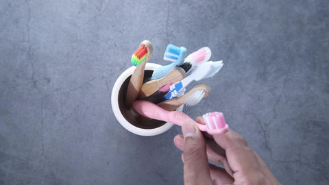 colorful toothbrushes in white mug on gray background Acción en vivo