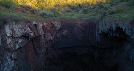 Huge natural pit with a man balancing on the slackline over it, 4k Acción en vivo