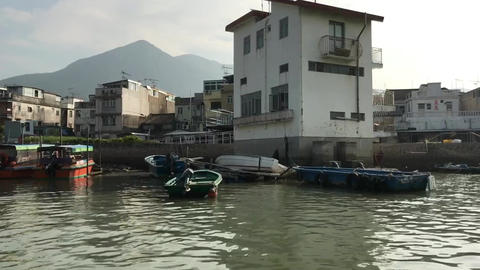 Hong Kong, China, A small boat in a body of water with buildings in the Acción en vivo