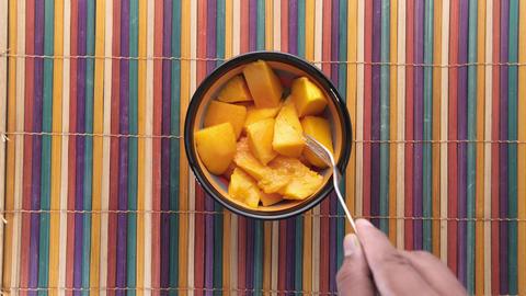 man eating yellow ripe cut mango top down Acción en vivo