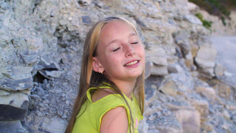Beautiful teenage girl sitting on rocks and smiling at camera Acción en vivo