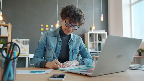 Beautiful businesswoman planning work writing in notebook in creative office Live Action