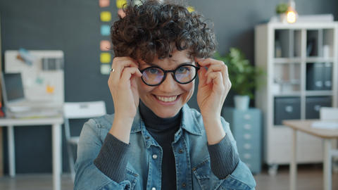 Portrait of beautiful woman putting on glasses and smiling looking at camera in Live Action