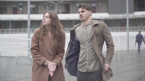 Confident loving boyfriend covering girlfriend from rain drops with coat Live Action