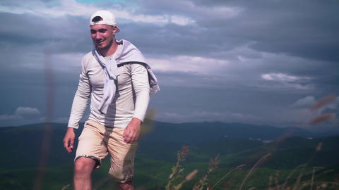 Young handsome man walking in the mountains Live Action