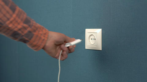 A Man Pulls Out a Phone Charger From a Wall Outlet Rosette in the Wall with Dark Blue Wallpaper Live Action