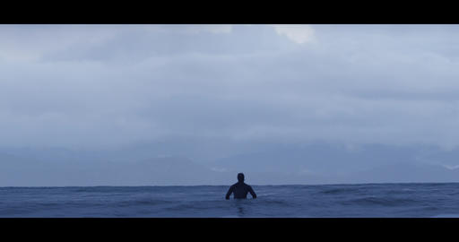 Surfer Sitting on Surfboard in the Ocean 4k 60fps Live Action