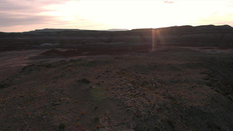 Flying towards sunset over rocky desert terrain in Mars Utah Live Action
